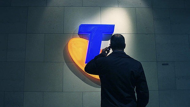 Telstra logo with man holding phone